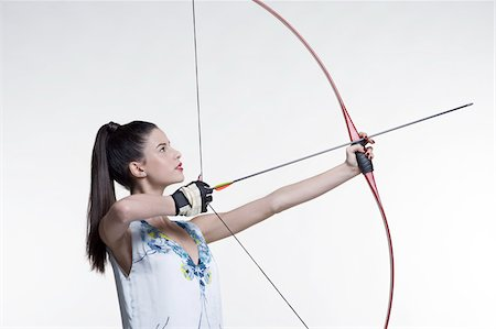 Side view of young, woman archer, aiming bow and arrow, studio shot on white background Stock Photo - Premium Royalty-Free, Code: 600-07066932