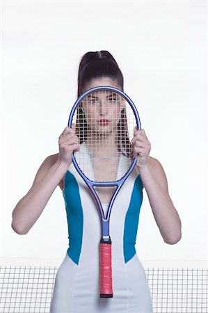 Portrait of young woman posing with tennis racket in front of face, studio shot on white background Stock Photo - Premium Royalty-Free, Code: 600-07066933