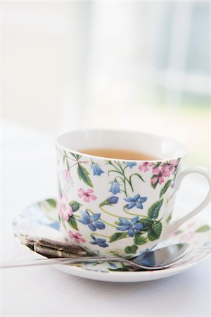 femininity - Cup of tea in pretty floral cup with saucer and used tea bag, studio shot Stock Photo - Premium Royalty-Free, Code: 600-07067016