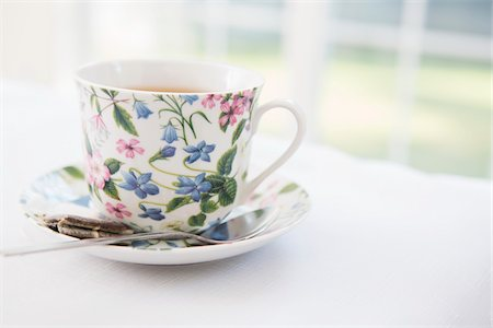 femininity - Cup of tea in pretty floral cup with saucer and used tea bag, studio shot Stock Photo - Premium Royalty-Free, Code: 600-07067017