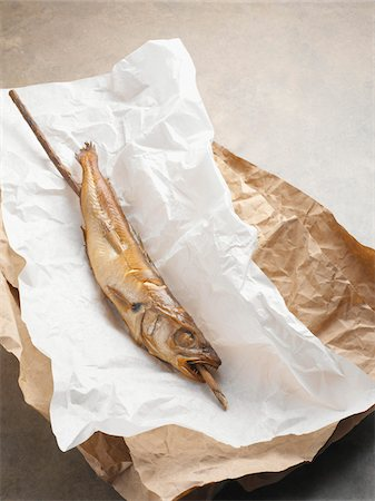 Fried mackerel pike fish on stick, in paper wrapper, studio shot Stock Photo - Premium Royalty-Free, Code: 600-07067122