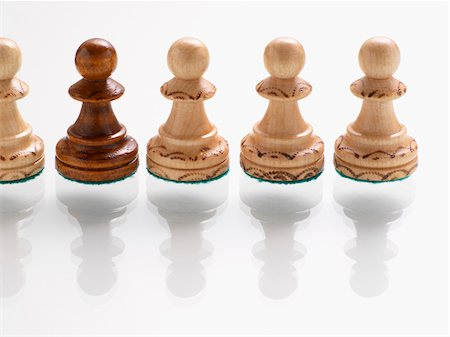 Dark wooden chess piece in row of light wooden chess pieces Stock Photo - Premium Royalty-Free, Code: 600-07067132