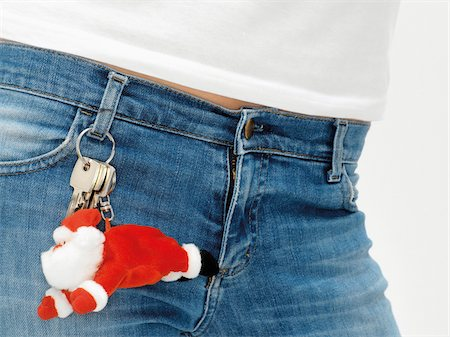 Close-up of waist with keychain shaped as Santa Clause hanging from belt loop, studio shot Stock Photo - Premium Royalty-Free, Code: 600-07067133