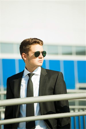 Young businessman wearing sunglasses, standing outdoors, Germany Stock Photo - Premium Royalty-Free, Code: 600-07117108