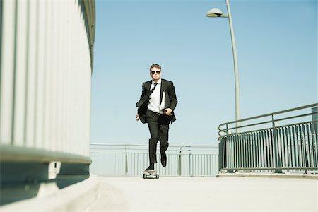 Businessman skateboarding on walkway holding binder, Germany Stock Photo - Premium Royalty-Free, Code: 600-07117115