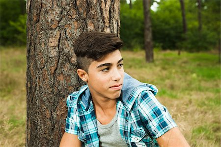 Close-up portrait of boy sitting beside tree in park, Germany Stock Photo - Premium Royalty-Free, Code: 600-07117116