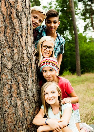 Portrait of group of children posing next to tree in park, Germany Stock Photo - Premium Royalty-Free, Code: 600-07117119