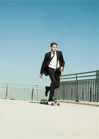 Businessman skateboarding on walkway holding binder, Germany Stock Photo - Premium Royalty-Free, Code: 600-07117113