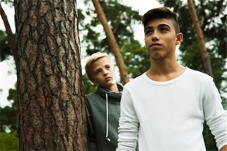 Portrait of two boys standing next to tree in park, Germany Stock Photo - Premium Royalty-Free, Code: 600-07117125