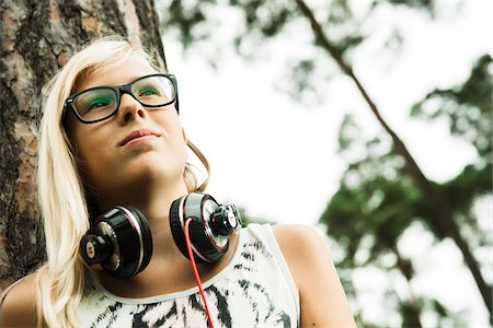 Portrait of girl wearing eyeglasses, standing next to tree in park, with headphones around neck, looking upward, Germany Stock Photo - Premium Royalty-Free, Code: 600-07117128