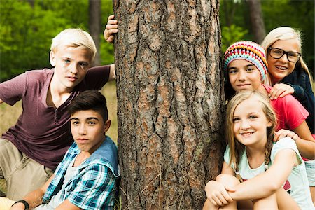 Portrait of group of children posing next to tree in park, Germany Stock Photo - Premium Royalty-Free, Code: 600-07117120