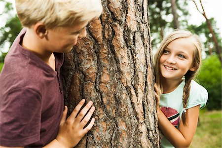 Boy and Girl playing outdoors standing next to tree in park, Germany Stock Photo - Premium Royalty-Free, Code: 600-07117121
