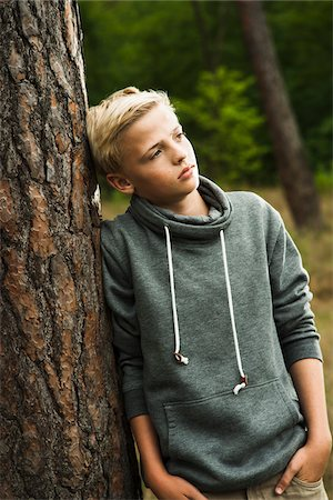 Portrait of boy standing in front of tree in park, looking into the distance, Germany Stock Photo - Premium Royalty-Free, Code: 600-07117123