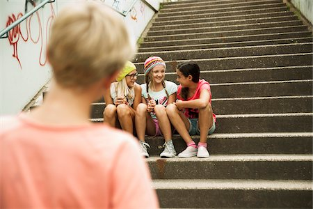 Backview of boy watching girls sitting on stairs outdoors, Germany Stock Photo - Premium Royalty-Free, Code: 600-07117156