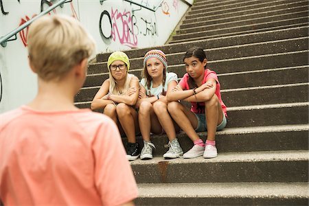 Backview of boy approaching girls sitting on stairs outdoors, Germany Stock Photo - Premium Royalty-Free, Code: 600-07117157