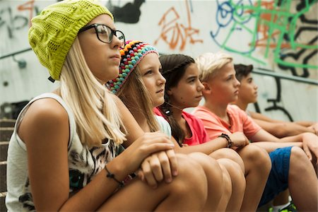 Group of children sitting on stairs outdoors, looking forward in the same direction, Germany Stock Photo - Premium Royalty-Free, Code: 600-07117159