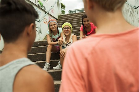 Backview of two boys talking to girls sitting on stairs outdoors, Germany Stock Photo - Premium Royalty-Free, Code: 600-07117167