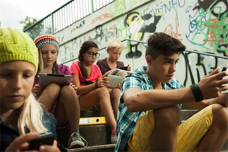 Group of children sitting on stairs outdoors, using tablet computers and smartphones, Germany Stock Photo - Premium Royalty-Free, Code: 600-07117168