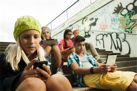 Group of children sitting on stairs outdoors, using tablet computers and smartphones, Germany Stock Photo - Premium Royalty-Free, Code: 600-07117169