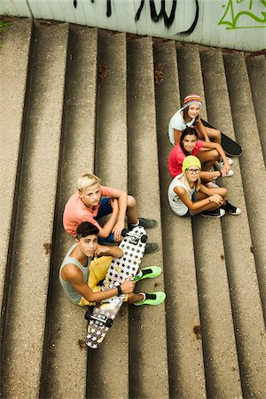 Group of children sitting on stairs outdoors, looking up at camera, Germany Stock Photo - Premium Royalty-Free, Code: 600-07117162