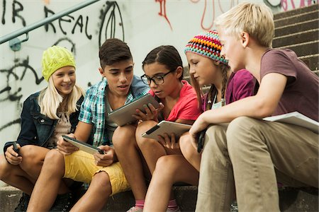 Group of children sitting on stairs outdoors, using tablet computers and smartphones, Germany Stock Photo - Premium Royalty-Free, Code: 600-07117175