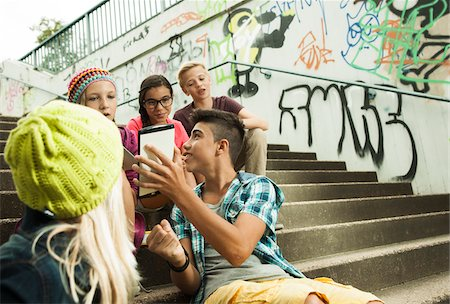 Group of children sitting on stairs outdoors, using tablet computers and smartphones, Germany Stock Photo - Premium Royalty-Free, Code: 600-07117170