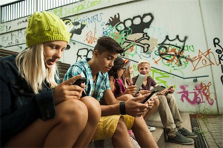Group of children sitting on stairs outdoors, using tablet computers and smartphones, Germany Stock Photo - Premium Royalty-Free, Code: 600-07117172