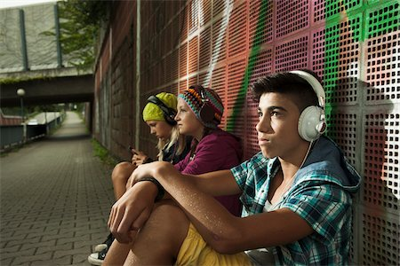 Children sitting next to wall outdoors, wearing headphones and listening to music, Germany Stock Photo - Premium Royalty-Free, Code: 600-07117180