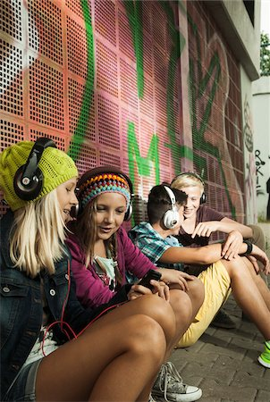 Group of children sitting next to wall outdoors, wearing headphones and listening to music, Germany Stock Photo - Premium Royalty-Free, Code: 600-07117181
