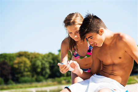 Boy and Girl using Cell Phone at Beach, Lampertheim, Hesse, Germany Stock Photo - Premium Royalty-Free, Code: 600-07117298