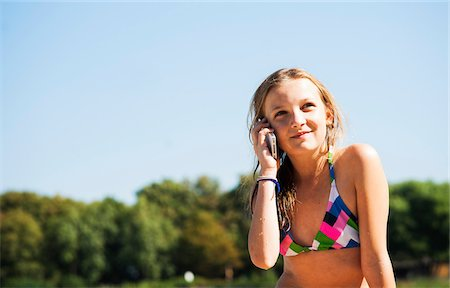 preteen bathing suit - Girl using Cell Phone at Beach, Lampertheim, Hesse, Germany Stock Photo - Premium Royalty-Free, Code: 600-07117299