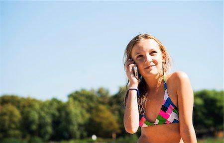 Girl using Cell Phone at Beach, Lampertheim, Hesse, Germany Stock Photo - Premium Royalty-Free, Code: 600-07117299