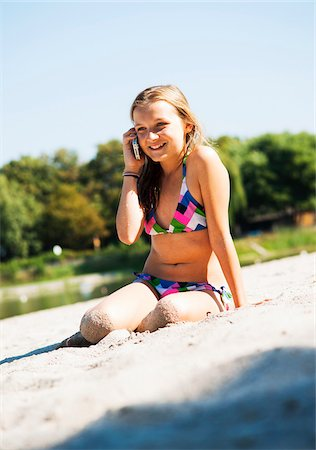 Girl using Cell Phone at Beach, Lampertheim, Hesse, Germany Stock Photo - Premium Royalty-Free, Code: 600-07117300