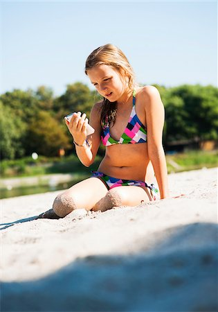 preteen bathing suit - Girl using Cell Phone at Beach, Lampertheim, Hesse, Germany Stock Photo - Premium Royalty-Free, Code: 600-07117301
