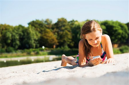 Girl using Cell Phone at Beach, Lampertheim, Hesse, Germany Stock Photo - Premium Royalty-Free, Code: 600-07117302