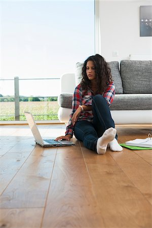 Teenage girl sitting on floor next to sofa, using laptop computer, Germany Stock Photo - Premium Royalty-Free, Code: 600-07148157