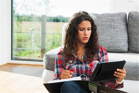 studying (all students) - Teenage girl sitting on floor next to sofa, writing in binder and using tablet computer, Germany Stock Photo - Premium Royalty-Free, Code: 600-07148158