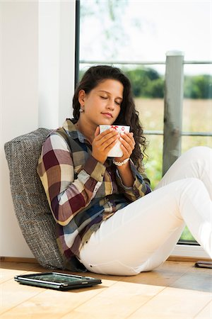 Teenage girl sitting on floor next to window, holding cup, Germany Stock Photo - Premium Royalty-Free, Code: 600-07148153