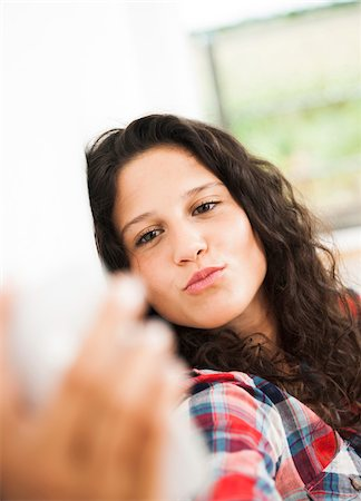 pucker - Teenage girl posing and taking selfie with smart phone, Germany Stock Photo - Premium Royalty-Free, Code: 600-07148168
