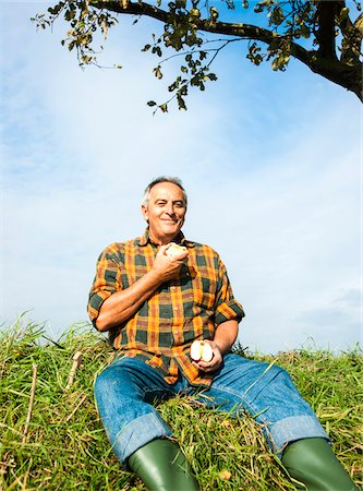 single fruits tree - Portrait of farmer sitting in field eating apple, Germany Stock Photo - Premium Royalty-Free, Code: 600-07148344