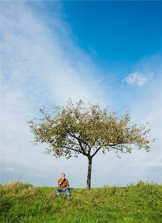 single fruits tree - Farmer sitting on hill next to apple tree, eating apple, Germany Stock Photo - Premium Royalty-Free, Code: 600-07148343