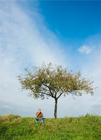 Farmer sitting on hill next to apple tree, eating apple, Germany Stock Photo - Premium Royalty-Free, Code: 600-07148343