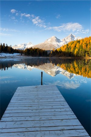 Jetty at Lake Staz with Larch Trees and Snow Covered Piz Nair Reflected in it in Autumn, Canton of Graubunden, Switzerland Stock Photo - Premium Royalty-Free, Code: 600-07143716