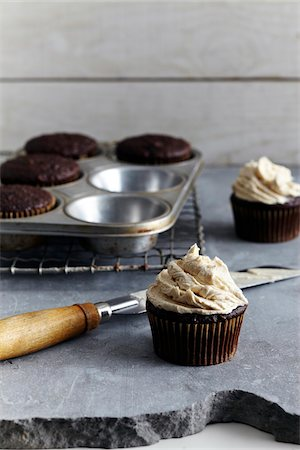 slate - Frosting freshly made cupcakes, studio shot Stock Photo - Premium Royalty-Free, Code: 600-07156146