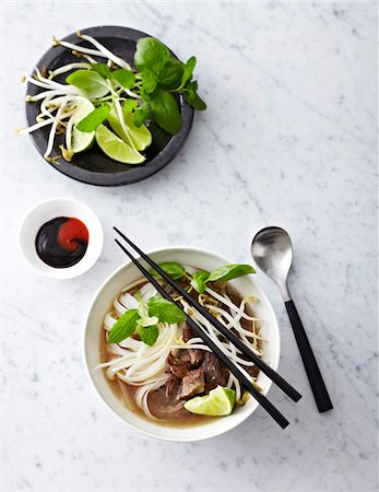 Beef Pho Noodle Soup in bowl with condiments, studio shot Stock Photo - Premium Royalty-Free, Code: 600-07156143