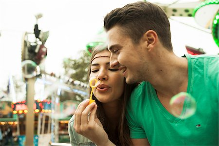Close-up portrait of young couple blowing bubbles at amusement park, Germany Stock Photo - Premium Royalty-Free, Code: 600-07156184