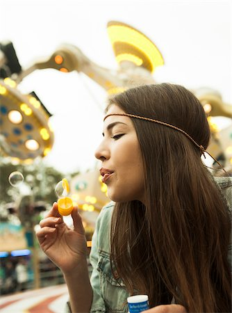 Close-up portrait of teenage girl blowing bubbles at amusement park, Germany Stock Photo - Premium Royalty-Free, Code: 600-07156185