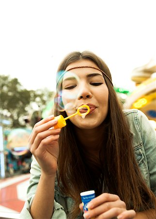female only - Close-up portrait of teenage girl blowing bubbles at amusement park, Germany Stock Photo - Premium Royalty-Free, Code: 600-07156186