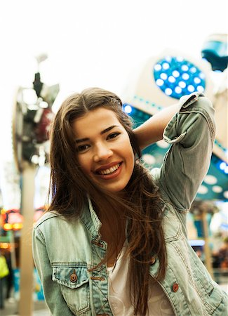 Close-up portrait of teenage girl at amusement park, looking at camera and smiling, Germany Stock Photo - Premium Royalty-Free, Code: 600-07156187