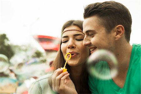 Close-up portrait of young couple blowing bubbles at amusement park, GermanyYoung Stock Photo - Premium Royalty-Free, Code: 600-07156183